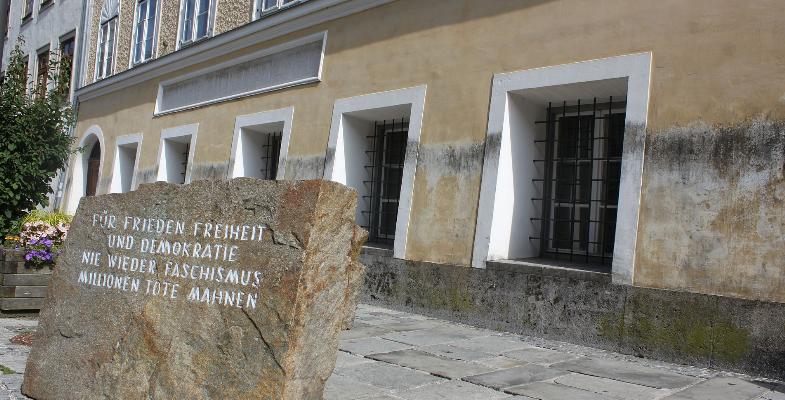 """Ein großer Stein mit den Worten """"Für Frieden Freiheit und Demokratie. Nie Wieder Faschismus. Millionen Tote Mahnen"""" steht vor dem Adolf Hitler Geburtshaus in der Salzburger Vorstadt 15 in Braunau am Inn. Ohne das Haus ist das Mahnmahl witzlos. (Bild: Wikimedia CC BY-SA 3.0 at)"""